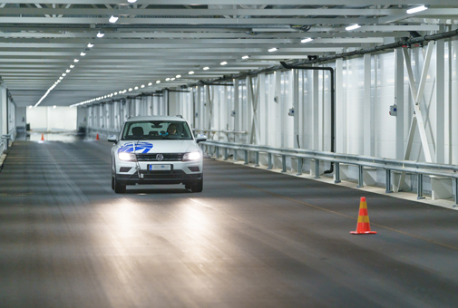 Car driving on dry asphalt in indoor cold weather test facility in Finland