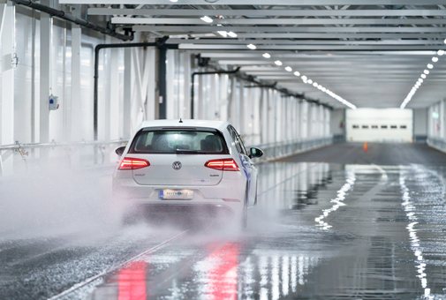 Indoor winter test track at Test World proving ground featuring R117-certified wet braking surface for tyre testing